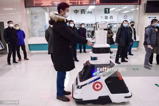 This photo taken on February 26, 2020 shows a patrol robot - used to check temperatures, identities and disinfect people - checking the identity of a...