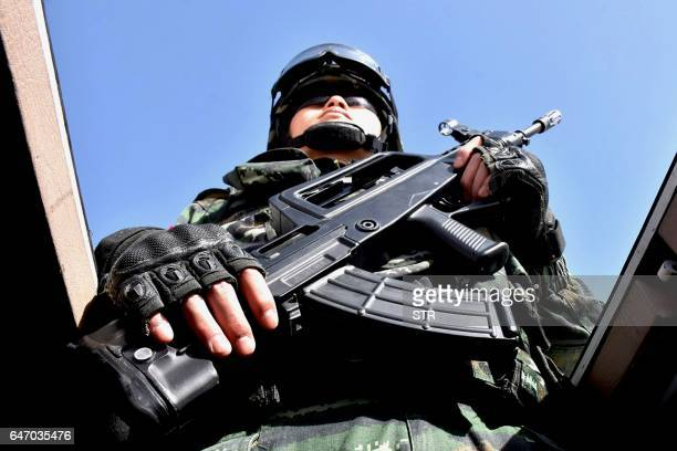 This photo taken on February 27 2017 shows a Chinese military policeman attending an antiterrorist oathtaking rally in Hetian northwest China's...