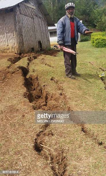 This photo taken on February 27 2018 and received on February 28 shows a man standing near cracks in the ground at Nipa in Papua New Guinea's...