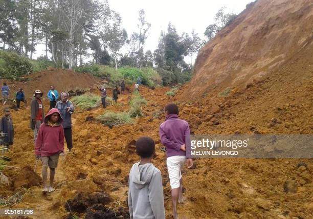 This photo taken on February 27 2018 and received on February 28 shows people walking at the site of a landslide near the village of Ekari in Papua...