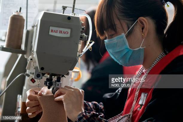 This photo taken on February 27 2020 shows facemaskclad workers stitching insoles at the Zhejiang Xuda Shoes Co factory in Wenzhou Only about...