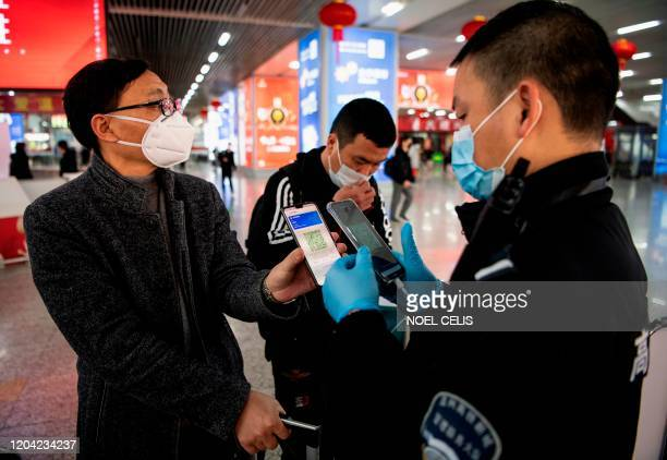 This photo taken on February 28, 2020 shows a passenger wearing a face mask as he shows a green QR code on his phone to show his health status to...