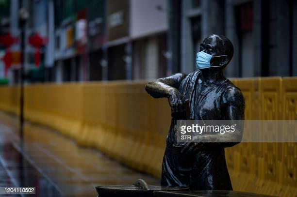 This photo taken on February 28 2020 shows a statue with a face mask on in Wuhan in China's central Hubei province China on February 29 reported 47...
