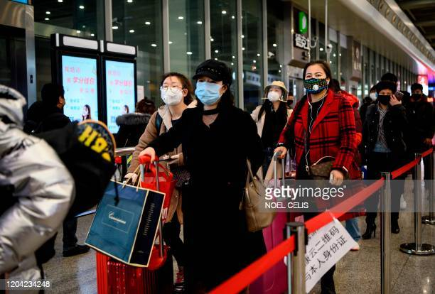 This photo taken on February 28, 2020 shows passengers wearing face masks arriving at Wenzhou railway station in Wenzhou. - The National Health...