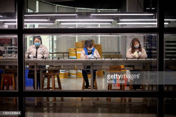 This photo taken on February 28 shows workers wearing facemasks polishing eyeglass frames at the Azure Eyeglasses Company in Wenzhou. - China's...