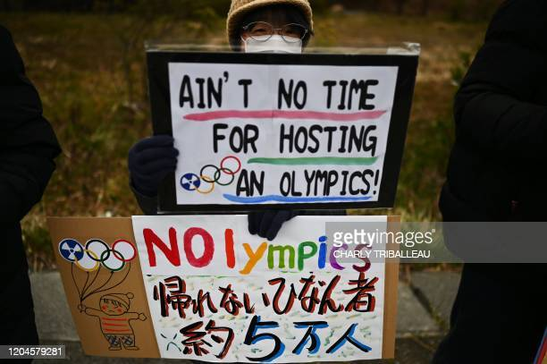 This photo taken on February 29, 2020 shows a protester holding placards during a demonstration against the Olympics, Prime Minister Shinzo Abe and...