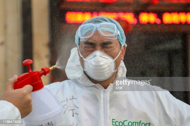 This photo taken on February 3, 2020 shows a doctor being disinfected by his colleague at a quarantine zone in Wuhan, the epicentre of the new...
