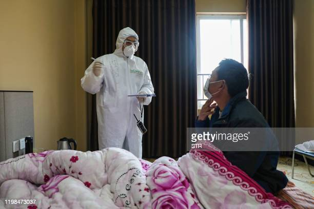 This photo taken on February 3, 2020 shows a doctor talking with a patient during his rounds at the ward of a quarantine zone in Wuhan, the epicentre...