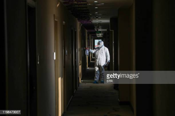 This photo taken on February 3, 2020 shows a medical staff member disinfecting at a quarantine zone converted from a hotel in Wuhan, the epicentre of...
