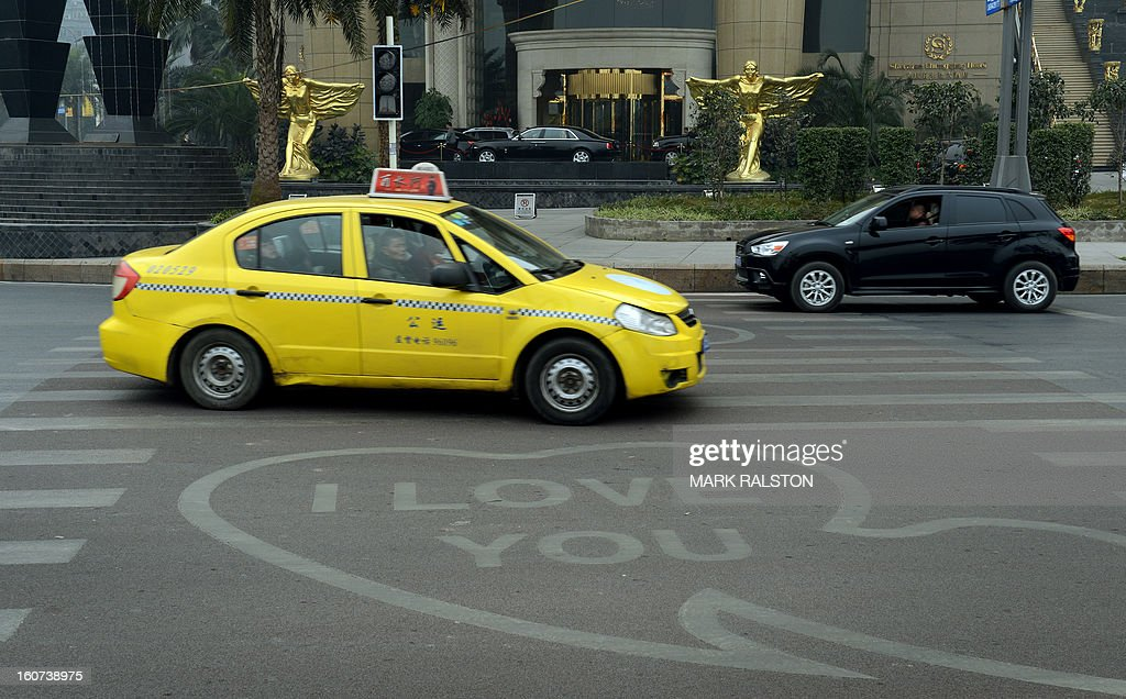 This photo taken on February 4, 2013 shows a taxi passing by 'I Love You' signs on a road crossing outside a hotel in the Nan'an district which was an area politically loyal to Bo Xilai and one of the two hotels where murdered British businessman Neil Heywood stayed at during his last week alive in Chongqing. Chinese state media has reported that Chongqing under the leadership of disgraced leader Bo Xilai raked up huge debts over his popularist transport infrastructure, social housing and construction projects. The reconstruction of the city of 32 million people however made Bo a popular figure amongst locals and made the Yangtze River city one of the world's fastest-growing urban area's. AFP PHOTO/Mark RALSTON