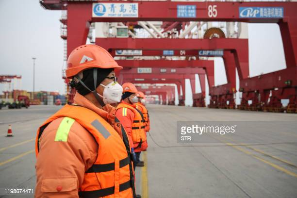 This photo taken on February 4 2020 shows Chinese employees wearing protective facemasks working at a port in Qingdao in China's eastern Shandong...