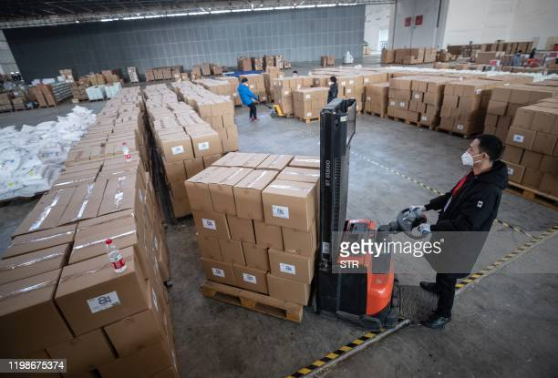 This photo taken on February 4 2020 shows staff members and and volunteers wearing protective face masks transferring medical supplies at a warehouse...