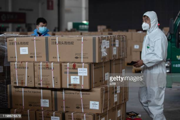 This photo taken on February 4 2020 shows staff members and volunteers transferring medical supplies at a warehouse of an exhibition centre which has...