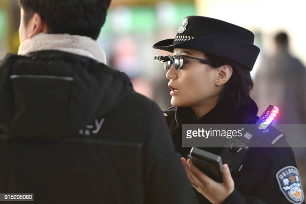 This photo taken on February 5 2018 shows a police officer speaking as she wears a pair of smartglasses with a facial recognition system at Zhengzhou...