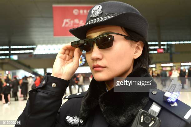 This photo taken on February 5 2018 shows a police officer wearing a pair of smartglasses with a facial recognition system at Zhengzhou East Railway...