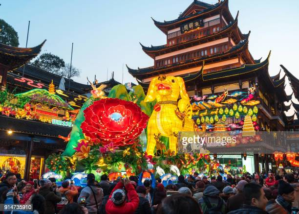 This photo taken on February 5 2018 shows people walking past a 9metre high dog lantern at the Yu Garden in Shanghai ahead of the coming Lunar New...
