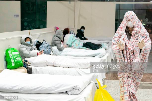 TOPSHOT This photo taken on February 5 2020 shows a patient covered with a bed sheet at an exhibition centre converted into a hospital as it starts...