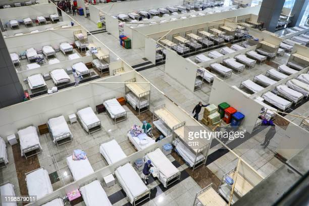 This photo taken on February 5, 2020 shows medical staff members and workers setting up beds as they prepare to accept patients displaying mild...