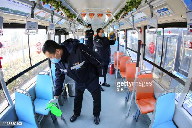 This photo taken on February 5, 2020 shows staff members disinfecting a bus in Qingdao, in China's eastern Shandong province, amid a virus outbreak...