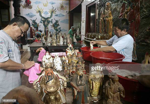This photo taken on February 6 2013 shows Indonesian devotees washing religious statues and figurines at a Buddhist temple in Surabaya located in...