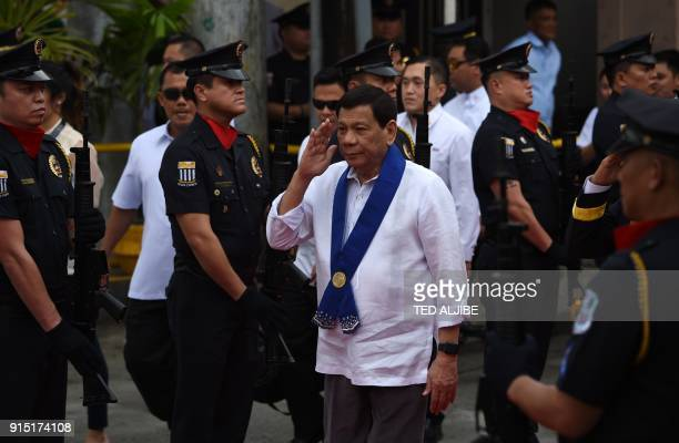 This photo taken on February 6 2018 shows Philippine President Rodrigo Duterte saluting as he arrives to attend the Bureau of Customs anniversary in...