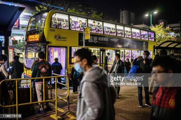 This photo taken on February 6 shows passengers disembarking from a bus shortly after their arrival in Tuen Mun in Hong Kong from Shenzhen, via the...