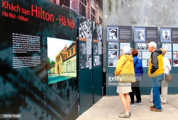 This photo taken on February 7 2018 shows tourists looking at an exhibition about US prisoners of war at the Hoa Lo prison dubbed the Hanoi Hilton...