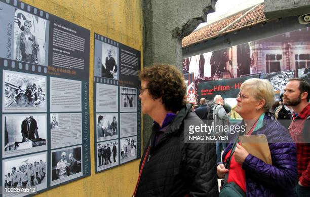 This photo taken on February 7 2018 shows tourists looking at photos of US Navy pilot John McCain at Hoa Lo prison dubbed the Hanoi Hilton now a...