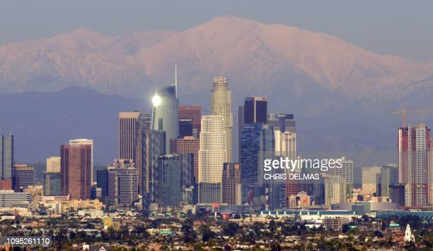 TOPSHOT This photo taken on February 7 2019 shows a view of the downtown Los Angeles skyline with the snowcovered San Gabriel Mountains in the...