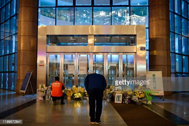 This photo taken on February 7 2020 shows a man bowing in front of flowers and a photo of the late ophthalmologist Li Wenliang outside the Houhu...