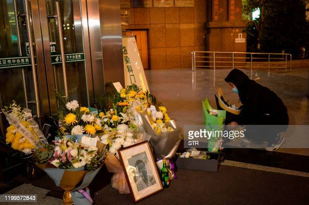 This photo taken on February 7 2020 shows a man placing flowers beside a photo of the late ophthalmologist Li Wenliang outside the Houhu Branch of...