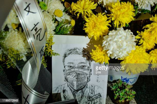This photo taken on February 7 2020 shows a photo of the late ophthalmologist Li Wenliang with flower bouquets at the Houhu Branch of Wuhan Central...
