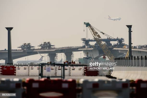 This photo taken on February 9 2017 shows a plane taking off from the international airport as construction work takes place on the Hong Kong Link...