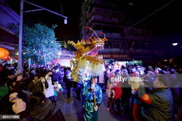 This photo taken on February 9 2017 shows people welcoming a traditional dragon dance to celebrate the upcoming Lantern Festival in Hangzhou east...
