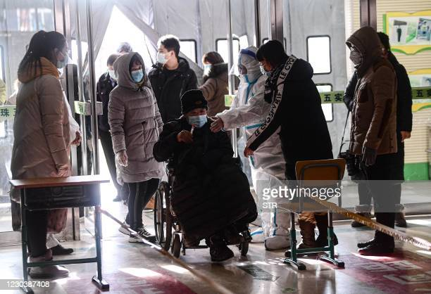 This photo taken on January 1, 2021 shows a a woman being wheeled into a COVID-19 coronavirus testing centre set up at a primary school in Shenyang,...