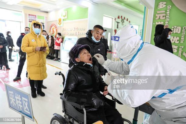 This photo taken on January 1, 2021 shows a woman undergoing a COVID-19 coronavirus swab test at a testing centre set up at a primary school in...