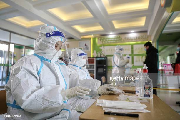 This photo taken on January 1, 2021 shows health workers preparing at a COVID-19 coronavirus testing centre set up at a primary school in Shenyang,...