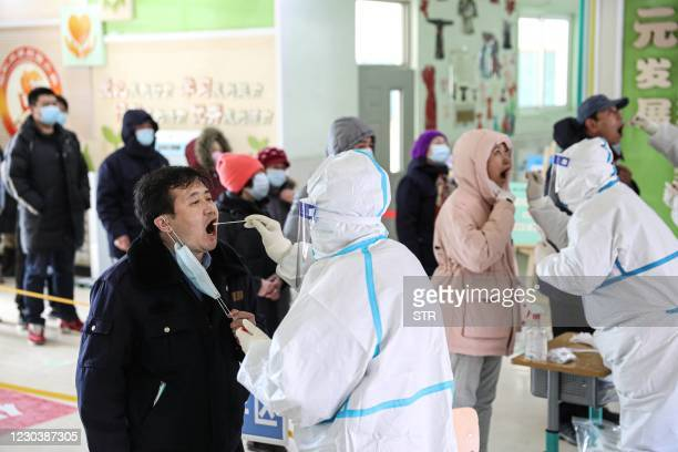 This photo taken on January 1, 2021 shows people undergoing COVID-19 coronavirus swab tests at a testing centre set up at a primary school in...