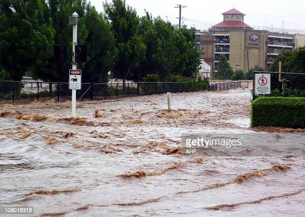 This photo taken on January 10 2011 shows people on the upper floors of a car park looking out as flood waters surge through streets inundating the...