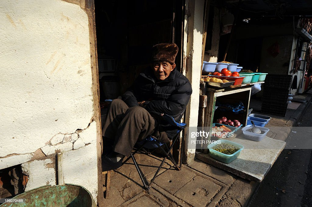 This photo taken on January 10, 2013 shows an elderly man with fruit and vegetables for sale on a street in Shanghai. China's inflation rate slowed to 2.6 percent in 2012, the National Bureau of Statistics said, down sharply from 5.4 percent the year before. AFP PHOTO/Peter PARKS