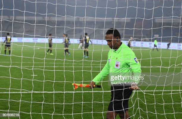 This photo taken on January 10 2018 shows an Indian referee inspecting a goal post before the Indian Super League football match between the Delhi...