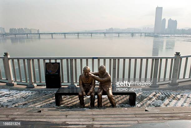 This photo taken on January 11 2013 shows a statue of a man comforting a person placed by the government to dissuade potential suicides at Mapo...