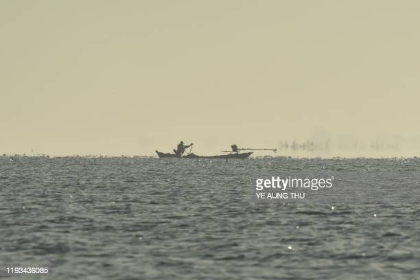 This photo taken on January 11, 2020 shows a fisherman on a boat at Moeyungyi wetlands in Bago Division, around 70 miles north of Yangon. - The lake...