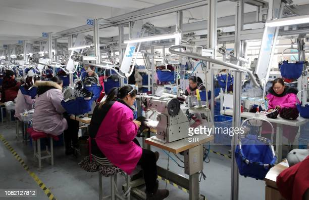 This photo taken on January 12 2019 shows workers making caps for export in a textile workshop in Lianyungang in China's eastern Jiangsu province...