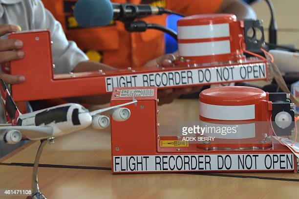This photo taken on January 13 2015 shows samples of the flight data recorder and the cockpit voice recorder during a press conference by Indonesian...
