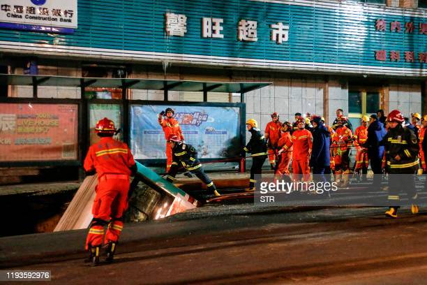 This photo taken on January 13, 2020 shows Chinese rescuers preparing to lift a bus after a road collapse in Xining in China's northwestern Qinghai...