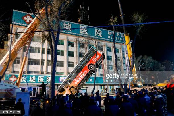 This photo taken on January 13, 2020 shows Chinese rescuers watching as a bus is lifted out after a road collapse in Xining in China's northwestern...