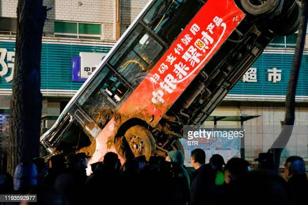 This photo taken on January 13, 2020 shows Chinese rescuers watching as a car is lifted out after a road collapse in Xining in China's northwestern...
