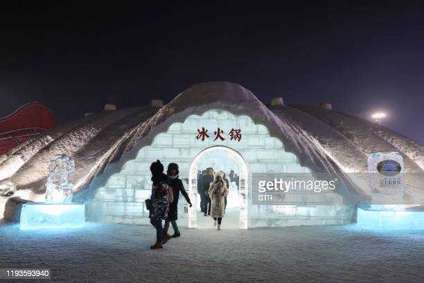 This photo taken on January 13 2020 shows people walking out of an igloo after enjoying hotpot in Harbin in China's northeastern Heilongjiang...