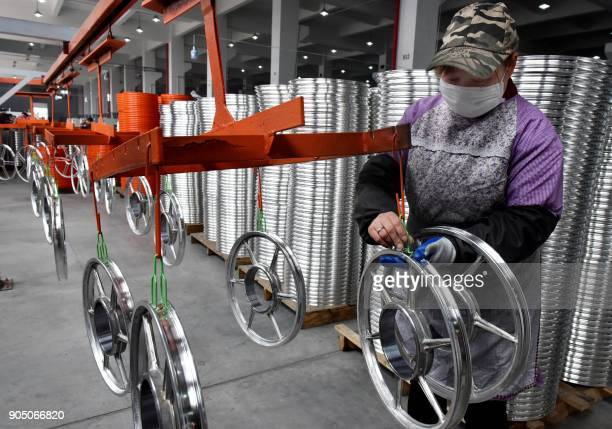 This photo taken on January 14 2018 shows a Chinese employee working on bicycle parts made for sharing bicycles at a factory in Jinhua in China's...